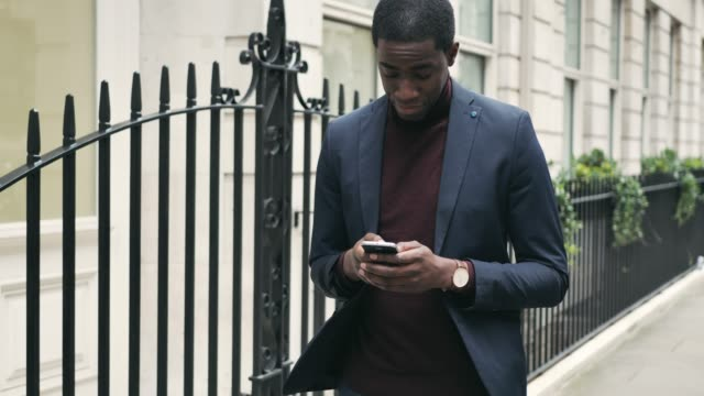 stockvideo's en b-roll-footage met volwassen afro-amerikaanse zakenman met behulp van telefoon terwijl het gaan werken - men blazer