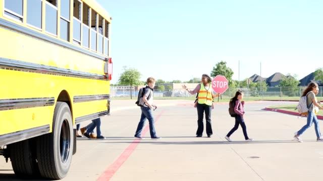 Mature African American female crossing guard helps school children cross street video