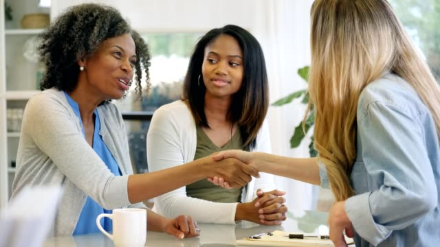vídeos y material grabado en eventos de stock de madura madre afroamericana e hija saludan terapeuta - saludar