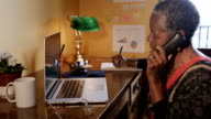 istock Mature African American woman talking on cordless phone in home office 1201319225