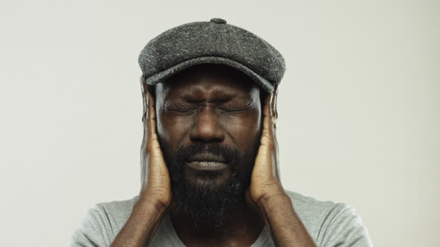 Mature african man gesturing hear no evil Close up video of mature african man covering his ears with his hands. Footage of real black man with beard gesturing hear no evil against gray background. Studio 4K RAW video with sharp focus on eyes. ear stock videos & royalty-free footage