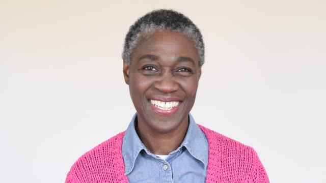 mogen afrikansk kvinna ler och vänder sig till ansikte kameran - mature women studio grey hair bildbanksvideor och videomaterial från bakom kulisserna