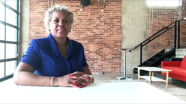 vídeos de stock e filmes b-roll de mature african-american businesswoman sitting at desk - portrait of confident business