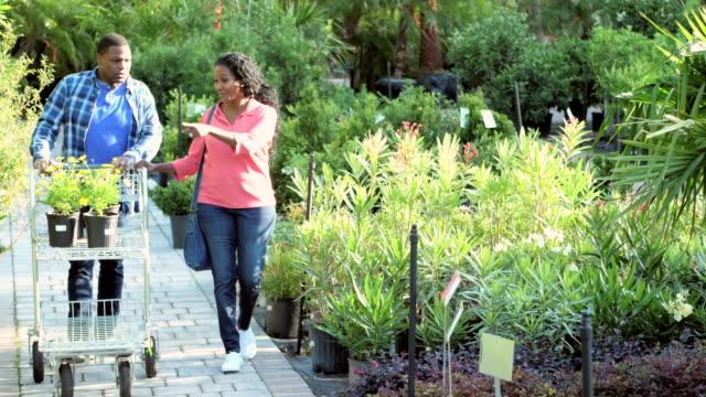 olgun afrikalı-amerikalı çift bitki kreş alışveriş - bahçe ekipmanları stok videoları ve detay görüntü çekimi