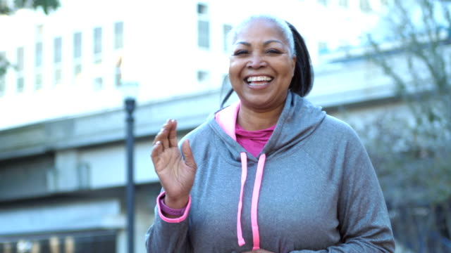 Mature African-American woman in city, ready to exercise A mature African-American woman in her 40s standing on a city street wearing sports clothing, ready to run, jog or power walk. She is looking at the camera, smiling, laughing, clapping hands, gesturing. sweatshirt stock videos & royalty-free footage