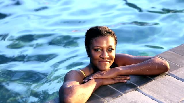 vidéos et rushes de femme afro-américaine mature dans la piscine, accrochée sur le côté - une seule femme d'âge mûr