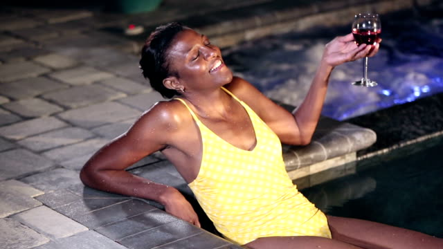 Mature African-American woman in pool relaxing at night A mature African-American woman in her 50s relaxing in a swimming pool, sitting on the steps, leaning back, looking away, thinking and smiling, holding a glass of wine.  It is nighttime. swimwear stock videos & royalty-free footage