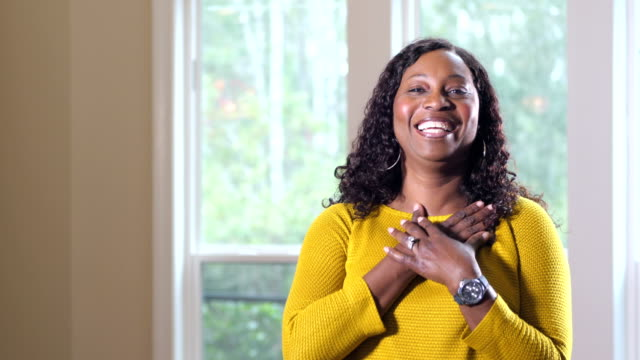 reife afroamerikanerin steht am fenster - dankbarkeit stock-videos und b-roll-filmmaterial