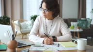 istock Mature american businesswoman working with design blueprint, watching laptop at desk in home office 1194623662