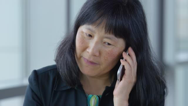 Mature Asian businesswoman using phone video