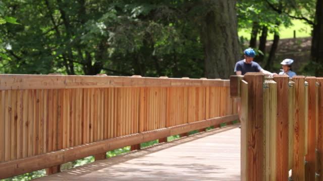 matura coppia asiatica equitazione tandem su ponte - coppia eterosessuale video stock e b–roll