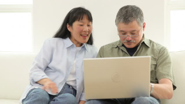 Mature Asian couple using laptop computer video