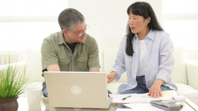 Mature Asian couple working on personal finances video