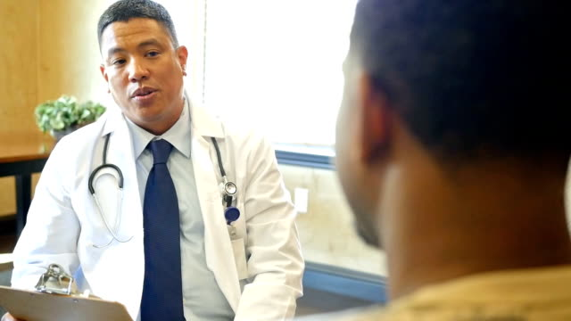 Mature Asian doctor talks with young African American male patient