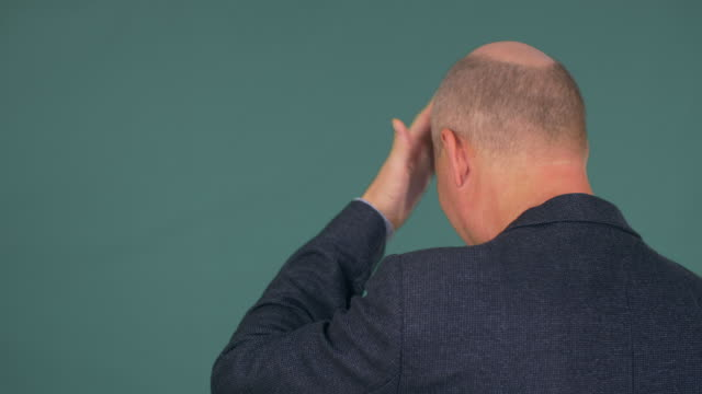 mature bald man dressed in smart suit slaps his forehead - głowa filmów i materiałów b-roll