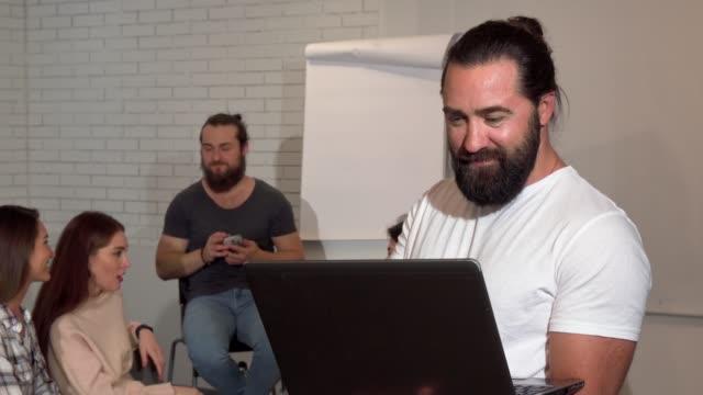 Hombre de negocios barbudo maduro usando computadora portátil, su equipo de negocios en el fondo - vídeo