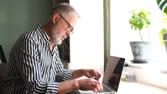mature bearded man working from home with laptop. sitting at desk near window Senior man at home in front of laptop computer working. Freelancer, on line worker fashionable stock videos & royalty-free footage