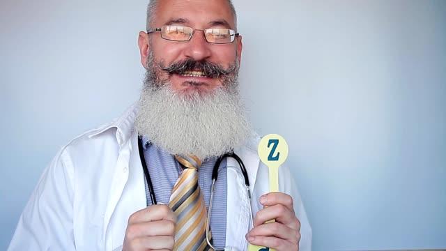 vidéos et rushes de l'orthophoniste barbu mature montre la lettre z et explique comment la prononcer correctement. bon docteur. fond gris. - professeur(e)