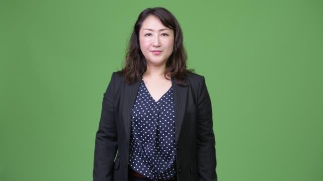 stockvideo's en b-roll-footage met rijpe mooie aziatische zakenvrouw tegen groene achtergrond - dameskostuum