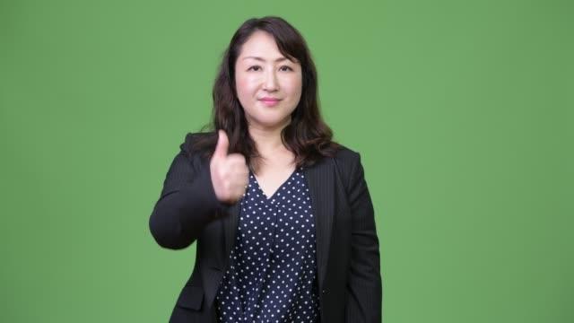 stockvideo's en b-roll-footage met rijpe mooie aziatische zakenvrouw geven duimen omhoog - dameskostuum