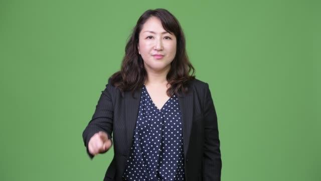stockvideo's en b-roll-footage met rijpe mooie aziatische zakenvrouw wijzende vinger omhoog - dameskostuum