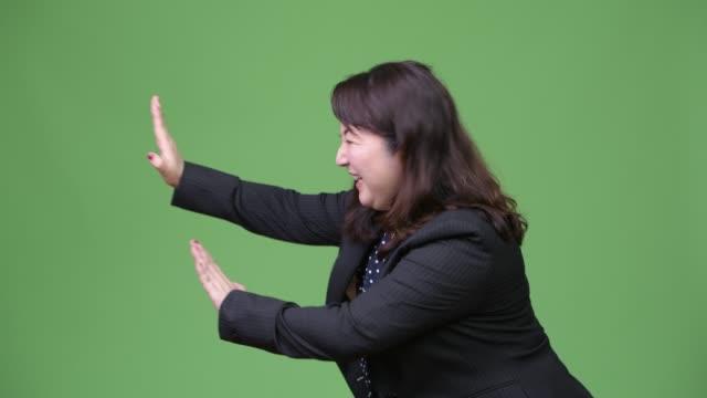 stockvideo's en b-roll-footage met rijpe mooie aziatische zakenvrouw zich verzetten tegen iets - dameskostuum