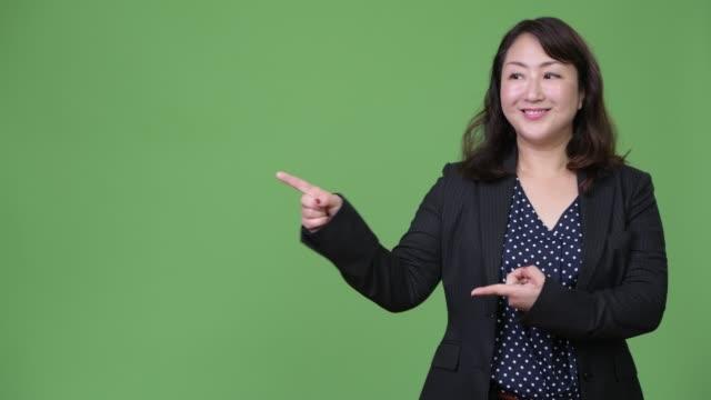 mogen vackra asiatiska affärskvinna visar något - kostym sida bildbanksvideor och videomaterial från bakom kulisserna