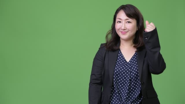 Mature beautiful Asian businesswoman showing something Studio shot of mature beautiful Asian businesswoman against chroma key with green background snapping stock videos & royalty-free footage