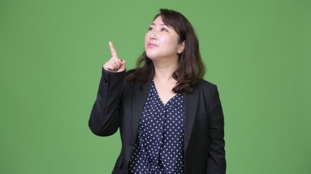 stockvideo's en b-roll-footage met rijpe mooie aziatische zakenvrouw bedenken terwijl wijzende vinger van - dameskostuum