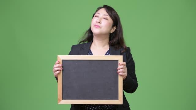 stockvideo's en b-roll-footage met rijpe mooie aziatische zakenvrouw denken terwijl weergegeven schoolbord - dameskostuum
