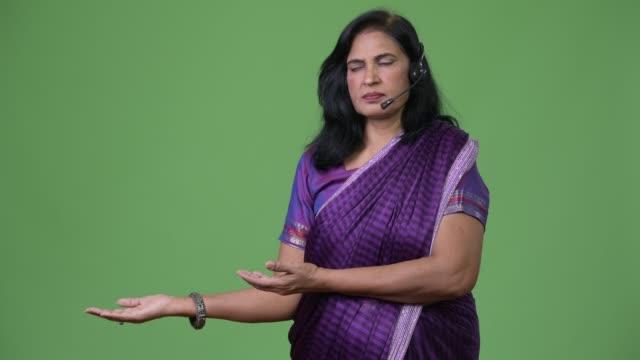 mature beautiful indian woman as call center representative showing something - sari filmów i materiałów b-roll