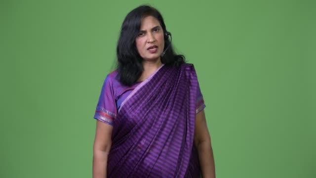 mature beautiful indian woman as call center representative talking on headset - sari filmów i materiałów b-roll