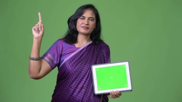 mature beautiful indian woman showing digital tablet and pointing finger up - sari filmów i materiałów b-roll