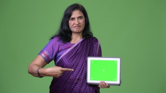 mature beautiful indian woman showing digital tablet and pointing finger - sari filmów i materiałów b-roll