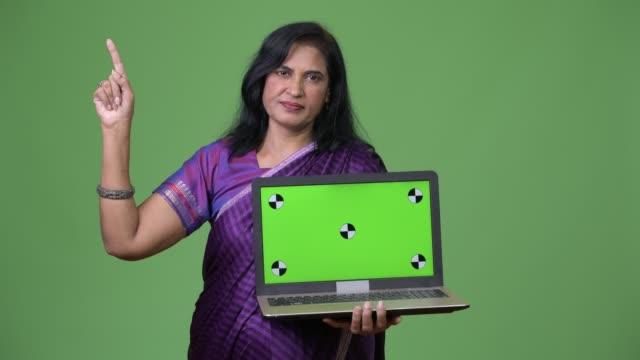 mature beautiful indian woman showing laptop and pointing up - sari filmów i materiałów b-roll