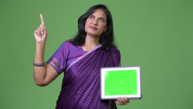 mature beautiful indian woman thinking while showing digital tablet and pointing finger up - sari filmów i materiałów b-roll