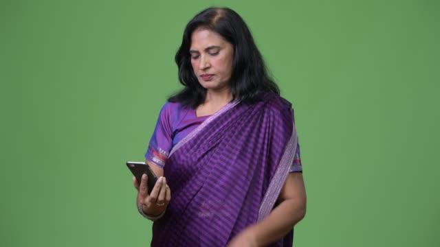 mature beautiful indian woman using phone - sari filmów i materiałów b-roll