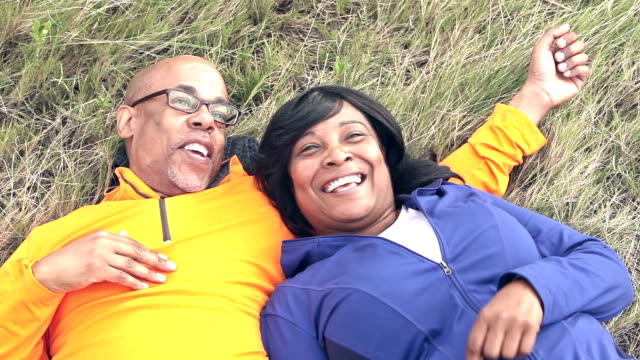 Mature black couple lying on grass, looking up video