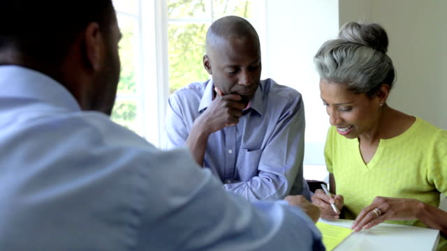 mature black couple meeting with financial advisor at home - tvåföräldersfamilj bildbanksvideor och videomaterial från bakom kulisserna