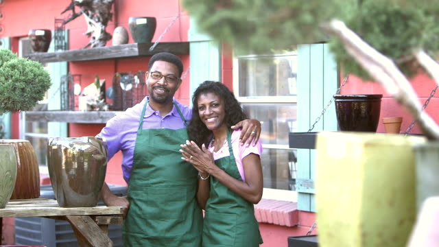 Mature black couple working in plant nursery Portrait of a mature black couple working in a plant nursery. They are successful small business owners, standing together, smiling confidently at the camera. plant nursery stock videos & royalty-free footage