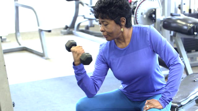 mature black woman at the gym lifting hand weight - sprzęt do ćwiczeń filmów i materiałów b-roll