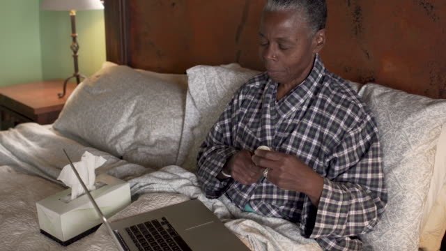 Mature black woman holding a pill bottle during a telemedicine appointment