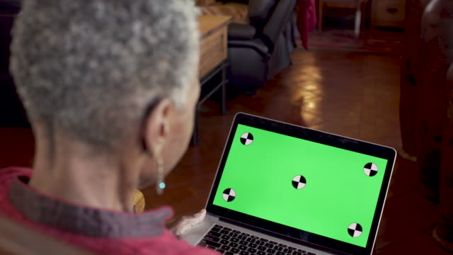 reife schwarze frau nickt ihren kopf ja beim blick auf einen grünen-bildschirm-computer - bloggen stock-videos und b-roll-filmmaterial