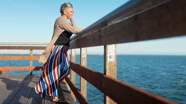 Mature black woman relaxing at the pier