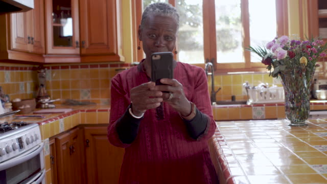Mature black woman rocking out in her kitchen using her cell phone