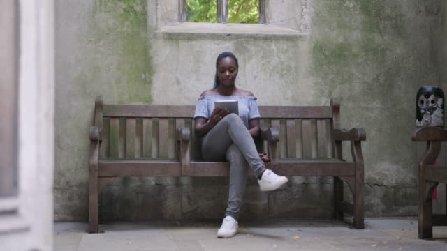 Mature Black woman sitting on a bench and using digital tablet to read a book in St Dunstan in the East video