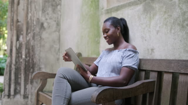 Mature Black woman sitting on a bench and using digital tablet to read a book in St Dunstan in the East
