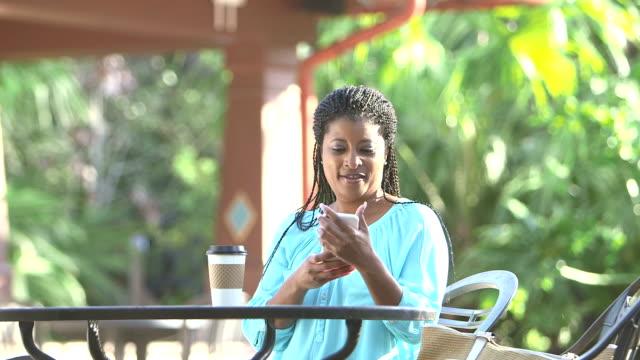 vidéos et rushes de femme noire mature s'approche de la table d'extérieur avec café - 40 44 ans