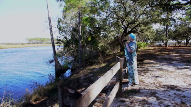 Mature body-positive woman watching birds with binocular in the Ochlockonee River State Park, North Florida