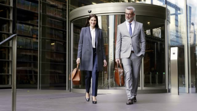 Mature business people leaving office after work